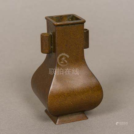 A small Chinese patinated bronze vase Of rounded spreading square section form with twin lug