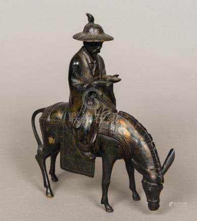 A 19th century Chinese patinated bronze group Formed as a scholarly figure seated atop a horse.