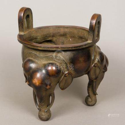 A large Chinese patinated bronze censer Of squat circular form, with twin loop handles,
