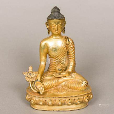 A gilt bronze model of Buddha Typically modelled seated in the lotus position holding a flower and