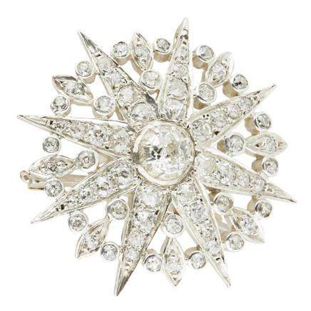A diamond set star brooch of traditional design, with a circular surround, set throughout with old
