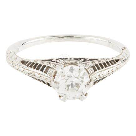 A single stone diamond ring claw set with a single old round cut diamond, in a pierced and raised