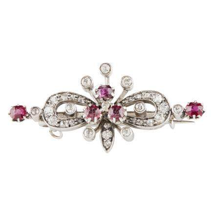 An Edwardian ruby and diamond set brooch of symmetrical form, claw set with a central group of three