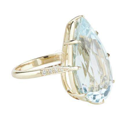 An aquamarine and diamond set cocktail ring claw set with a pear shaped aquamarine, each shoulder