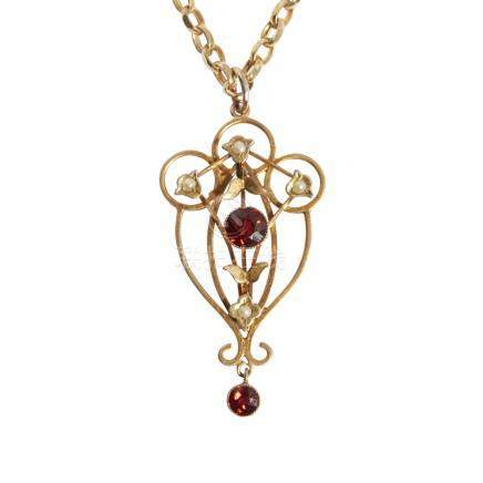 An Edwardian garnet and seed pearl set pendant of open scrolling design, set with seed pearls and