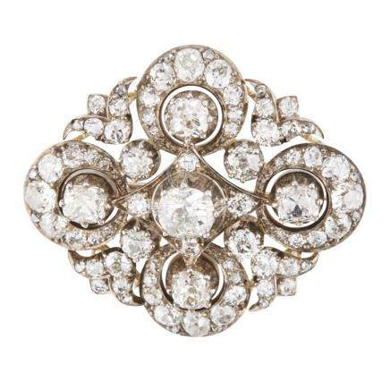 A 19th century diamond set brooch claw set with a cushion cut diamond, in a stylised surround of