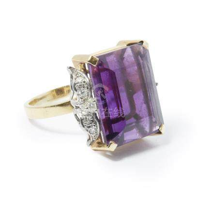 An amethyst set cocktail ring claw set with a large rectangular cut amethyst, each shoulder set with