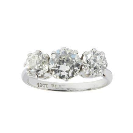 A three stone diamond ring claw set with three graduated old round cut diamonds, to a plain shank
