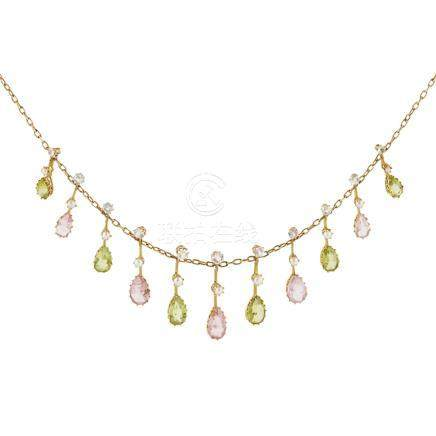 An Edwardian peridot and tourmaline set fringe necklace the trace link chain suspending eleven
