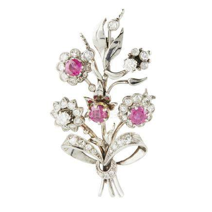 A ruby and diamond set spray brooch modelled as a ribbon tied spray of flowers, set throughout