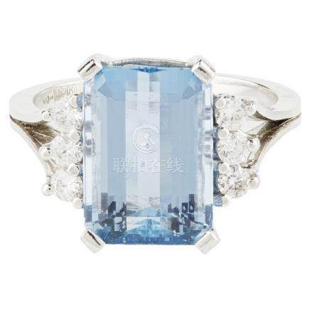 An aquamarine and diamond dress ring claw set with an emerald cut aquamarine, flanked by three round