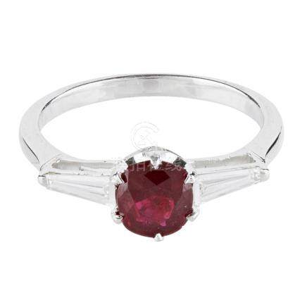 A ruby and diamond set ring claw set with a cushion cut ruby, each shoulder set with a tapered