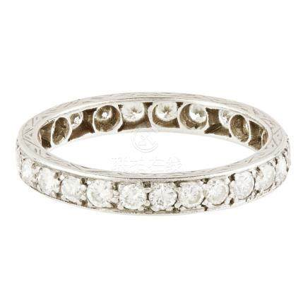 A diamond set eternity ring claw set with a continuous row of small round brilliant cut diamonds,