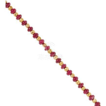 A ruby bead necklace comprised of twenty-four polished ruby beads of graduated sizes between faceted
