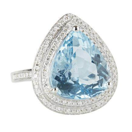 A topaz and diamond set cluster ring claw set with a pear-shaped blue topaz, in a double border of
