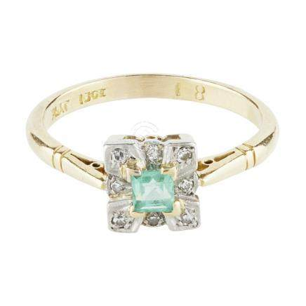 An Art Deco emerald and diamond set ring claw set with a square cut emerald in a border of pavé
