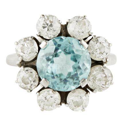 A zircon and diamond set cluster ring claw set with a round cut blue zircon, in a border of old
