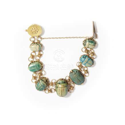 A scarab beetle bracelet composed of seven graduated glazed ceramic scarab beetles with