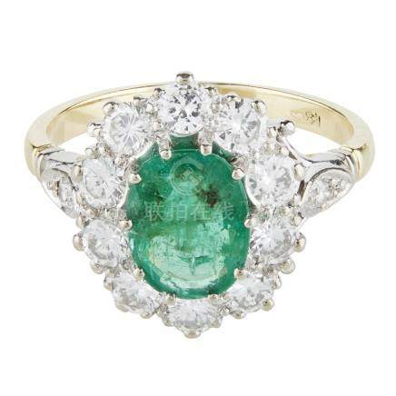 An emerald and diamond set cluster ring claw set with an oval cut emerald in a border of round
