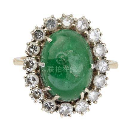 An emerald and diamond set cluster ring claw set with an oval emerald cabochon, in a single border
