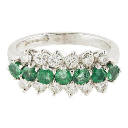 An emerald and diamond set ring claw set with a row of seven round cut emeralds, between two rows of