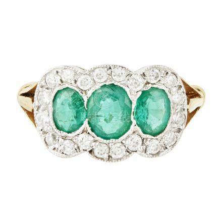 An emerald and diamond triple cluster ring comprised of three mixed oval cut emeralds millegrain set