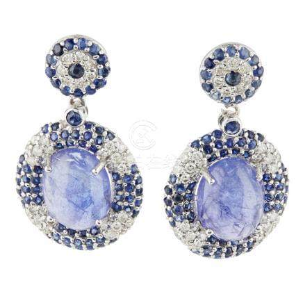 A pair of Tanzanite, sapphire and diamond set pendant earrings each claw set with an oval cut