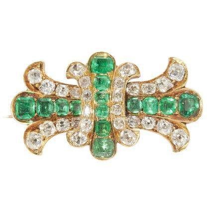 An emerald and diamond set brooch of stylised design, composed of two intersecting sets of two old