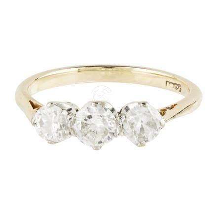 A three stone diamond ring claw set with three graduated round brilliant cut diamonds, to a plain