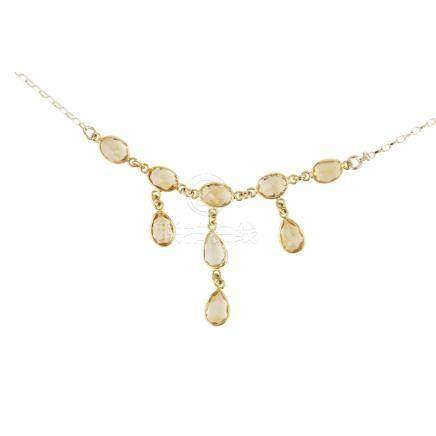 A citrine necklace the trace link chain collet set with five oval cut citrines, suspending three