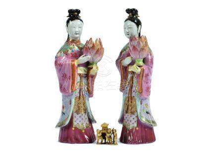 A pair of Chinese figural candlesticks, each modelled as a woman in pink robe holding a lotus