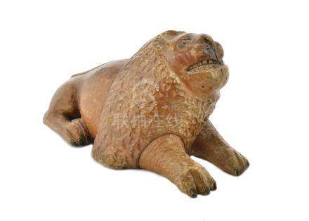 An early 20th Century Asian carved wooden stylised model of a recumbent lion, 50 cm long