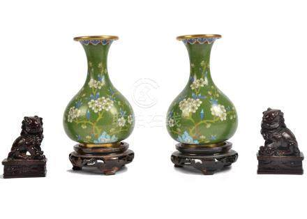 A pair of 20th Century cloisonne vases, floral decoration on green ground, hardwood stands, 19 cm