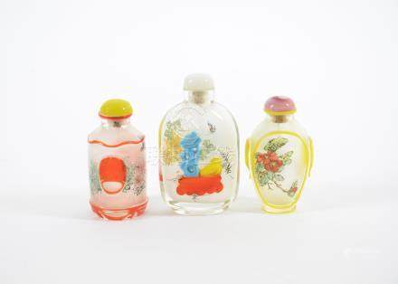 Three 20th Century Chinese reverse painted glass snuff bottles, comprising a floral decorated