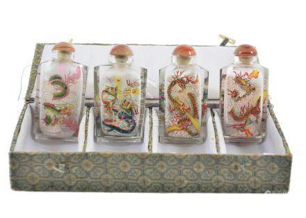 A cased set of four 20th Century Chinese reverse painted scent bottles, each decorated with dragons,