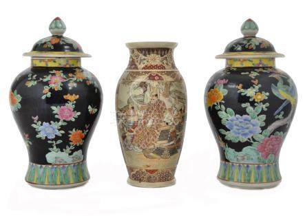 A pair of 20th Century Japanese baluster vases with covers, each decorated with a pair of peacocks
