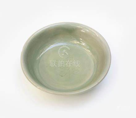 Plat en porcelaine émaillé céladon orné d'une fleur avec son feuillage en motif