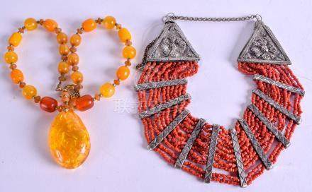 AN EARLY 20TH CENTURY TIBETAN CORAL NECKLACE together with an amber type necklace. (2)