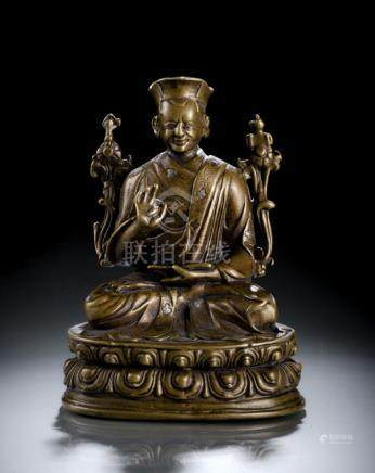 A SILVER- AND COPPER-INLAID BRONZE FIGURE OF A LAMA, TIBET, 14th/15th ct., seated in vajrasana on a