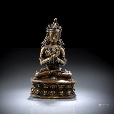 A GILT-BRONZE FIGURE OF VAJRADHARA, Tibet, 15th ct., Seated in vajrasana on a lotus base with both h