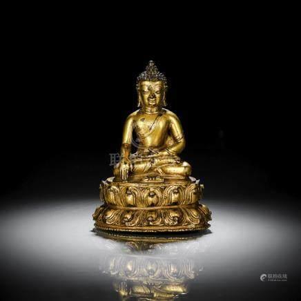 A GILT-BRONZE FIGURE OF BUDDHA SHAKYAMUNI, TIBET, 15th ct., seated in vajrasana on a lotus base with