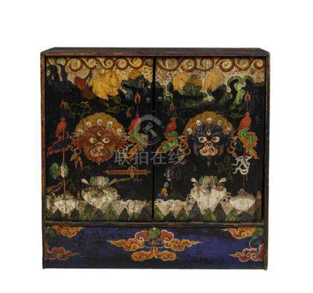 A POLYCHROME PAINTED BLACK-GROUND TORMA CABINET, Tibet, ca. 1900, the rectangular cabinet has a pair