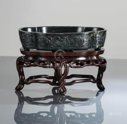 A SPINACH-GREEN CARVED FOUR-LOBED JADE BOWL ON A CARVED WOOD STAND, China, late Qing/Republic period