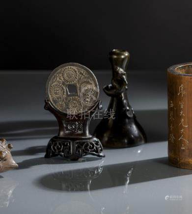 A BRONZE COIN ON A WOOD STAND AND A BRONZE DRAGON VASE, China, Qing dynasty - The coin worn, the vas