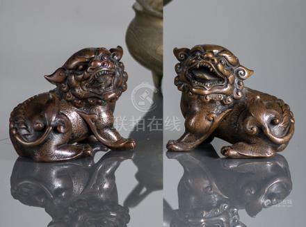 A PAIR OF SILVER-INLAID BRONZE LIONS, China, 19th/20th ct. - Wear, losses to inlays