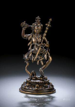A  SILVER- AND COPPER-INLAID BRONZE FIGURE OF VAJRAVARAHI, TIBET, standing in dancing posture on a f