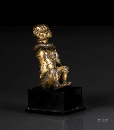 A GILT-BRONZE FIGURE OF A MONKEY, CHINA, Ming dynasty, cast in squatting posture with both knees rai