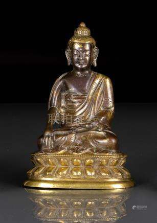 A PARCEL GILT-BRONZE FIGURE OF BUDDHA SHAKYAMUNI, TIBETO-CHINESE, 18th/19th ct., seated in vajrasana