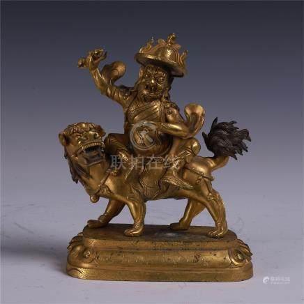 TIBETAN GILT BRONZE BUDDHIST GUARDIAN ON LION