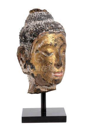 A GILT AND PAINTED STONE BUDDHA HEAD